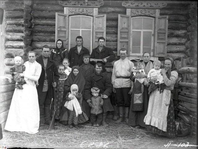 Групповое фото житeлей одного из сёл Енисейской губернии. Кто-то пришёл фотографироваться с ружьём, кто-то с балалайкой. Российская империя. 1910 год