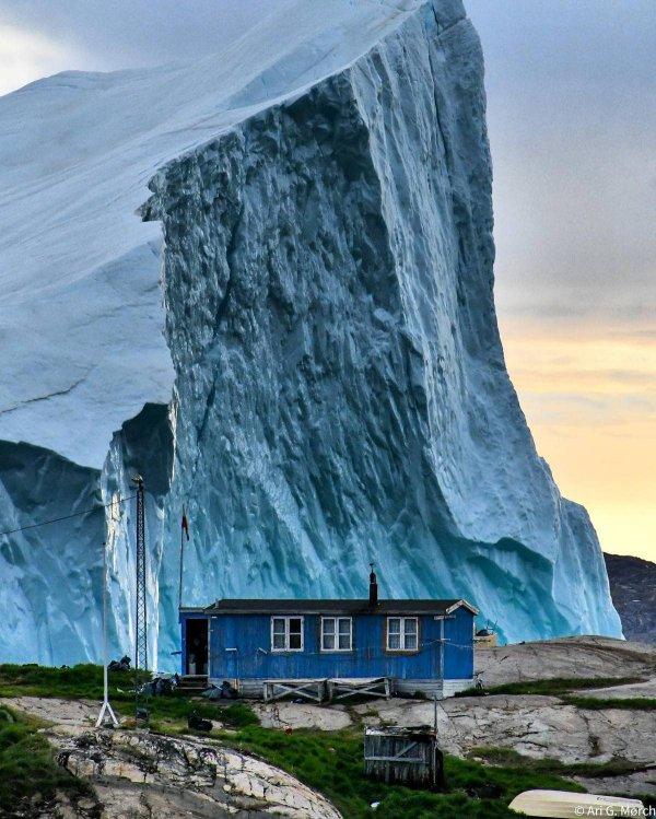Огромный айсберг проплывает мимо домика в Гренландии