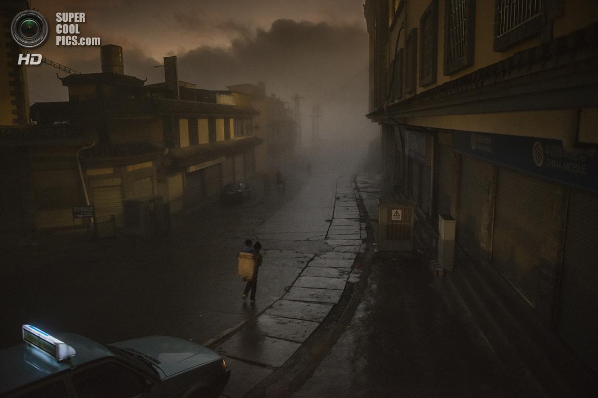 Победитель в номинации «Места». Понимая, что в скором времени этот старый город будет преобразован в новый мегаполис и, возможно, потеряет свою сырую красоту, я был рад, что смог запечатлеть эту трудягу-мать, несущую ребёнка в корзине сквозь густой туман очень ранним утром. Место съемки: Китай. Юаньян, Юньнань. (Adam Tan/National Geographic Photo Contest)