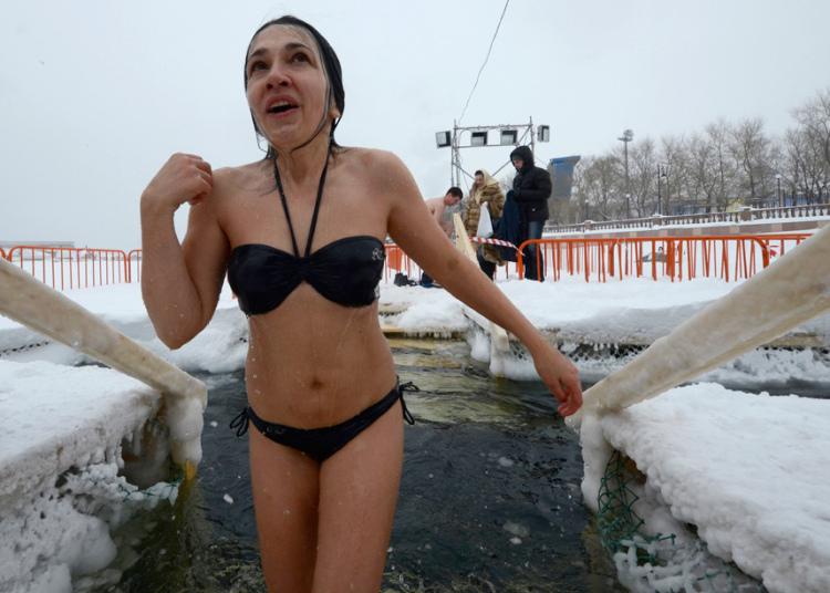 3. Девушка традиционно крестится после купания в ледяной воде.